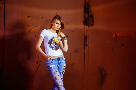 Beautiful young model woman in jeans and handmade shirt is sensually touching hair at red urban rusty gate background.