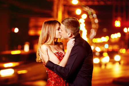 Beautiful young woman in red sparkling dress is passionately kissing elegant macho man at city street at bright lights blurred background. photo
