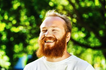 riendo: Primer retrato de hombre maduro feliz con la barba roja y el bigote se est� riendo en Parque de verano fondo verde.