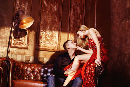 Beautiful glamour young couple is kissing in bedroom sitting on sofa.