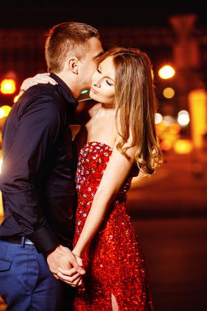 novios besandose: Primer retrato de la hermosa joven pareja besándose en la noche calle de la ciudad en las luces de colores de fondo. Foto de archivo