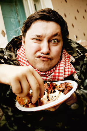 squint: Portrait of greedy hungry chewing man with squint eye taking piece of fat meat from a plate at kitchen background.