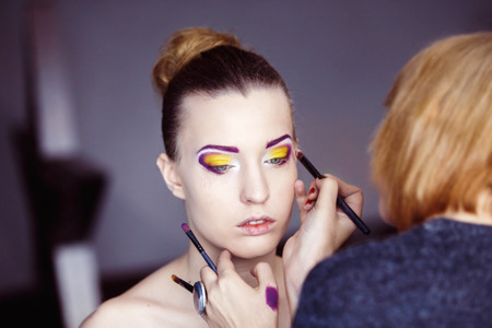 Professional makeup process. Artist is making face style of a young beautiful model at  lilac studio background. photo