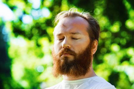 Крупным планом портрет человека с рыжей бородой и глазами при закрытых зеленом фоне парке летом. Концепция благополучия, расслабления и медитации. Фото со стока