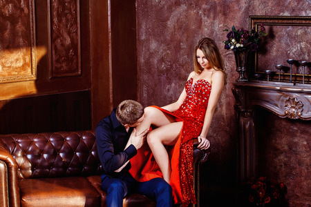 Elegant young man is kissing his beautidul young wife in red dress in bedroom.