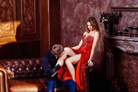 pareja apasionada: Hombre joven elegante está besando a su joven esposa beautidul en vestido rojo en el dormitorio.