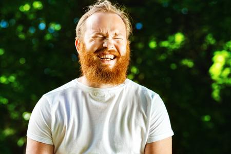 reir: Primer retrato de hombre maduro feliz con la barba roja y el bigote se está riendo en Parque de verano fondo verde.
