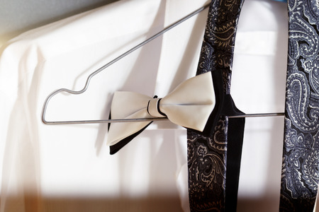 neckcloth: Coseup image of elegant necktie and white shirt hanging in wardrobe at wall background.