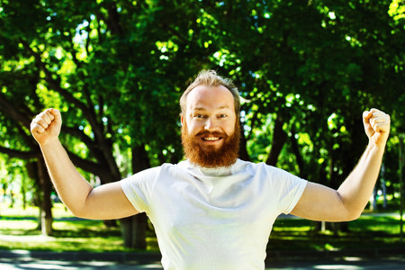 Счастливый человек с рыжей бородой кладет руки вверх, как жест успеха, достижения на зеленом фоне летнего парка.
