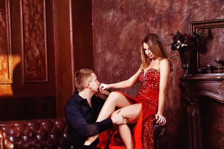 pareja apasionada: Hombre joven elegante está besando a su niña beautidul en vestido rojo en el dormitorio. Foto de archivo