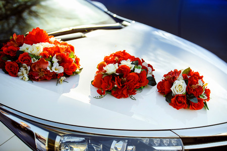 arreglo floral: Imagen de detalle de la decoración del coche de la boda con flores rojas y blancas ramo Foto de archivo