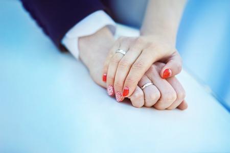 Imagen de detalle de las manos del hombre y la mujer con el anillo de bodas que sostiene con ternura en el fondo azul.