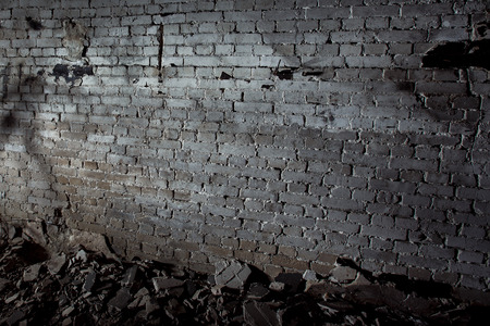 Image of grey aged ruined dark wall with concrete pieces on floor. Concept of horror movie.