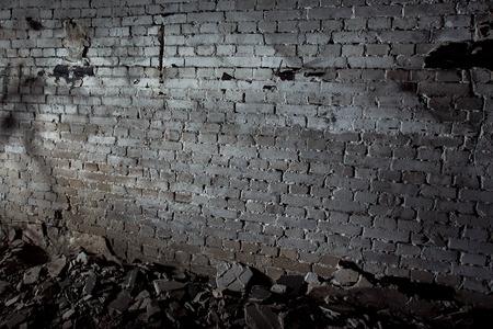 Hình ảnh của bức tường tối màu xám già bị hủy hoại với các mảnh bê tông trên sàn nhà. Khái niệm về bộ phim kinh dị.