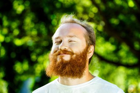 Bức chân dung cận cảnh của người đàn ông trưởng thành hạnh phúc với bộ râu và ria mép đang mỉm cười với nền công viên cây xanh mùa hè.