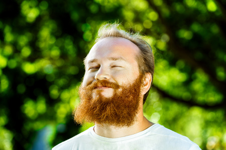 Closeup portrait of happy mature man with red beard and mustache is smiling at summer green park background.