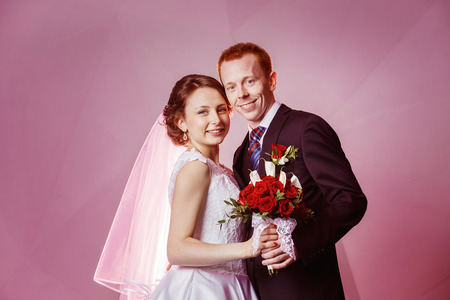 bride and groom background: Happy smiling wedding couple holding red roses flowers bouquet at pink wall background.