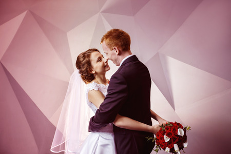 rose photo: Portrait of beautiful young wedding couple kissing at pink textured wall indoors background.