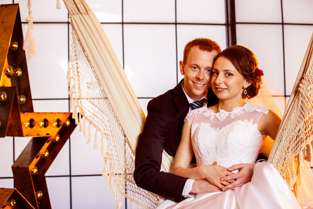 wedding couple: Happy beautiful wedding couple is smiling swinging in hammock at window with yellow star background.