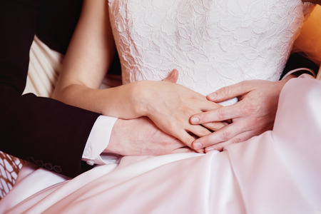 tenderly: Closeup portrait of wedding couple tenderly holding by hands