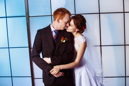 lovingly: Portrait of beautiful young wedding couple with closed eyes holding hands lovingly at bright blue window background. Stock Photo