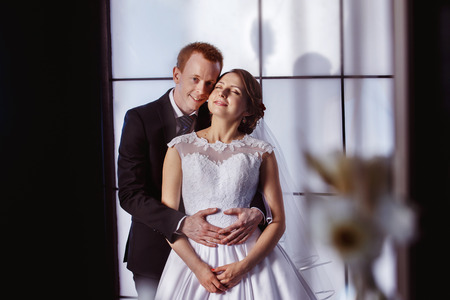 lovingly: Portrait of young elegant groom holding his beautiful bride with closed eyes lovingly at window background.