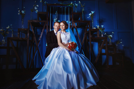 lovingly: Portrait of handsome groom lovingly holding beautiful wife with red roses bouquet at blue background.