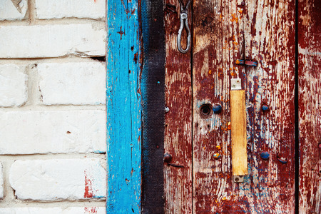 scaled: A wooden vintage scaled red door with handle and blue aperture at white bricks background.