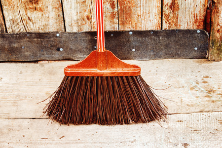 besom: Closeup image of old red broom at vintage wooden wall and door background. Stock Photo