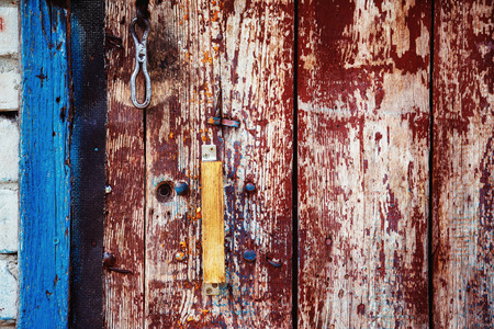 scaled: A wooden vintage scaled red door with handle and blue aperture as retro background.