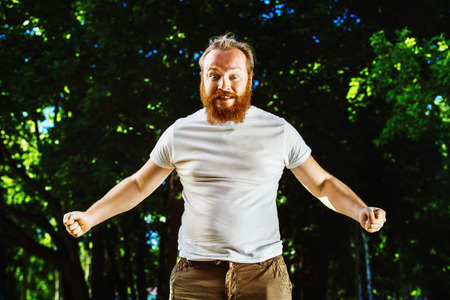 tightened: Portrait of young angry man with red hair and beard is standing with tightened fists at green natural summer park background. Stock Photo