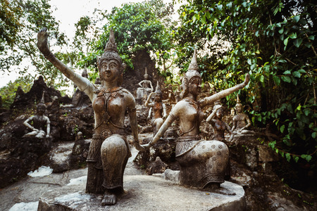 secret place: Row of old statues in secret buddhist garden. Concept of mysterious place for relaxation and meditation.