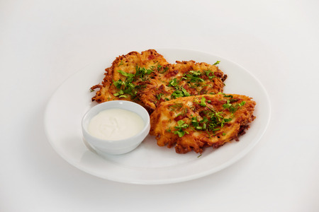 vegeterian: Plate of fried brown vegeterian potato pancakes with cup of cream isolated at white background. Nationail Russian meal.