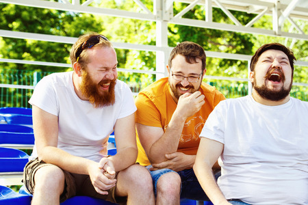 Three young cheerful friends are talking and laughing at summer day stadium background. Standard-Bild