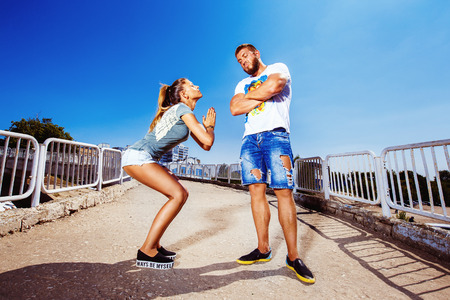 sexy man: Young attractive girl is asking her man for forgiving making common gesture at summer bright background. Stock Photo