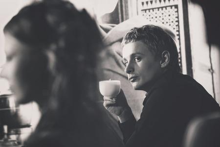 sexuel: Portrait of élégante macho avec tasse de café Coolink à belle fille au rétro fond de mur.