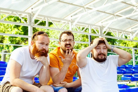 three day beard: Three bearded football fan friends are sitting upset at goal moment at summer stadium  background.