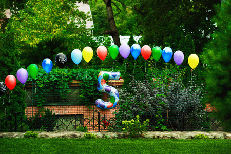 baloons: Green summer park decorated for colorful birthday party with baloons having shape of number five. Stock Photo