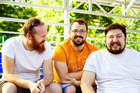 Трое молодых веселых друзей, которые говорили и смеялись на летний день стадиона фоне. Фото со стока