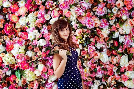 ni�o modelo: Primer retrato de la hermosa modelo preadolescente ni�a de pie con ramo de las flores cerca de la pared de fondo colorido floral.