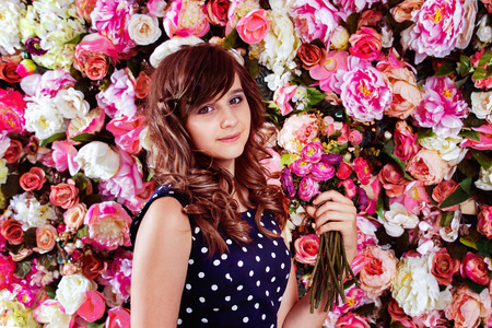 little model: Closeup portrait of beautiful preteen girl model standing with flowers bouquet near colorful floral wall background. Stock Photo