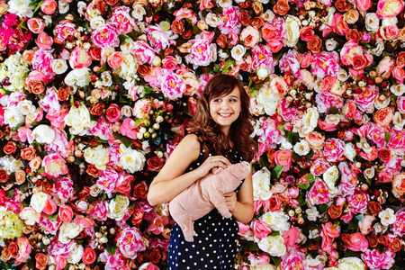 child model: Beautiful preteen girl model is laughing with pink pig toy near colorful floral wall background. Stock Photo