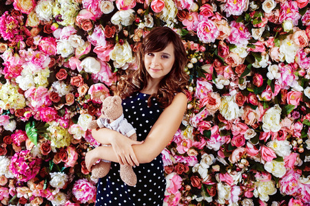 clothing model: Beautiful preteen girl model is standing with bear toy near colorful floral spring wall background.
