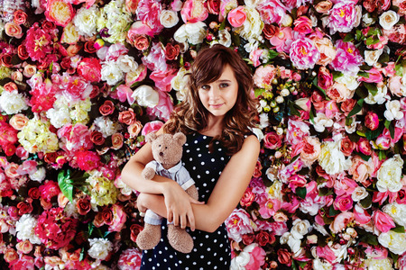 preteen model: Beautiful preteen girl model is standing with bear toy near colorful floral wall background. Stock Photo