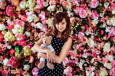 little model: Beautiful preteen girl model is standing with bear toy near colorful floral wall background. Stock Photo