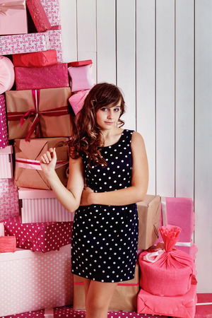 beauty girls: Happy pretty preteen girl in dress is standing at pink gift boxes heap at white wall background. Stock Photo