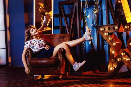 modelos posando: Hermosa niña preadolescente está sentado sonriente en un sillón en el interior de fondo. Foto de archivo
