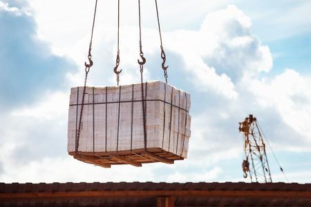 Closeup image of crane lifting heap of bricks at blue sky summer background.