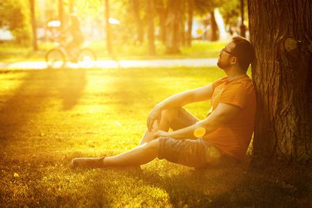 Счастливая вдумчивый мечтатель человек сидит на зеленой траве в парке в солнечный летний день, и, глядя в будущее. Концепция релаксации, благополучия, образа жизни.