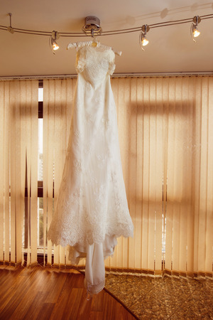 lustre: Beautiful luxury white wedding dress is hanging on lustre at window background.